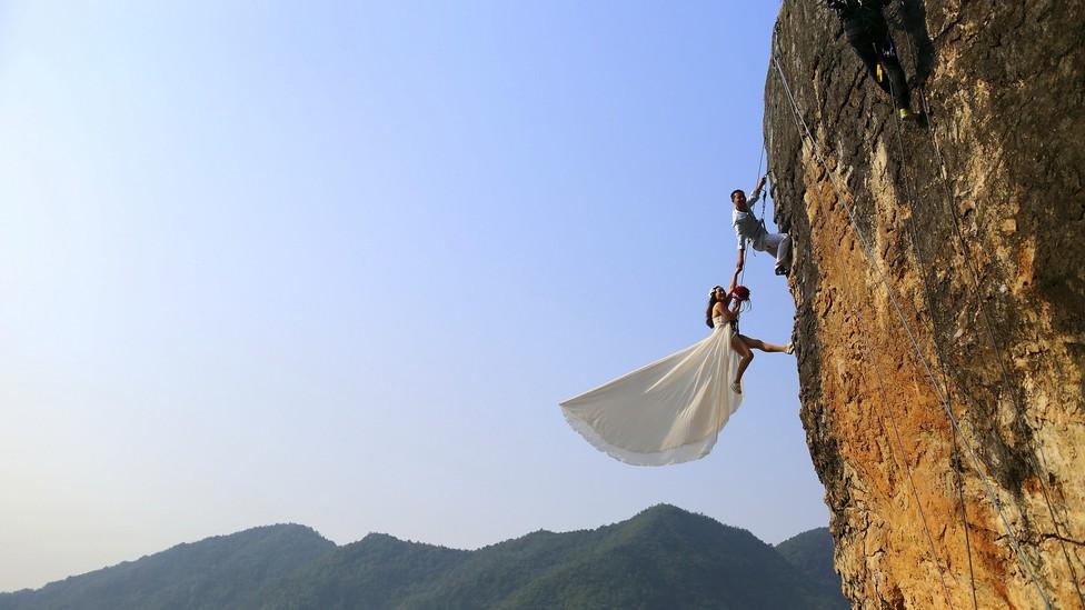 A woman in a wedding dress climbing a mountain