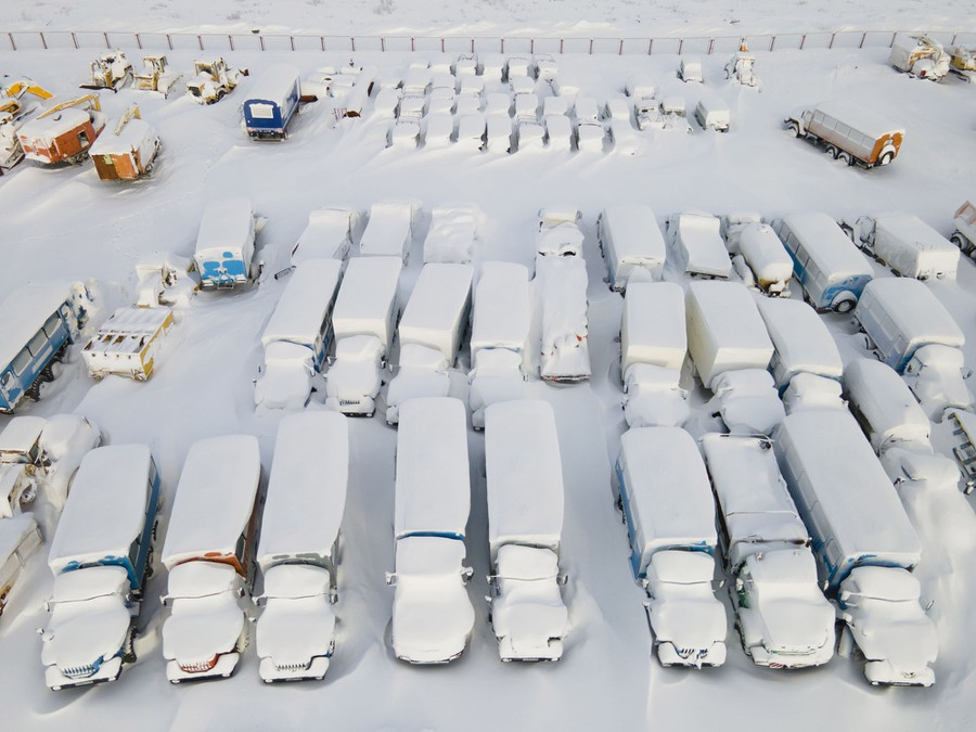 Snow-covered trucks and heavy equipment sit in a parking lot.