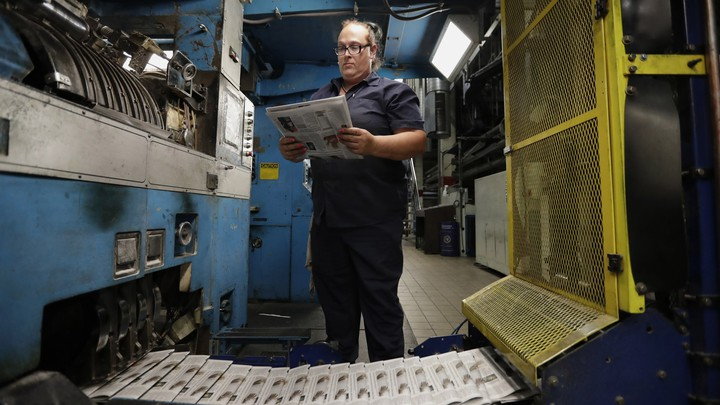 An employee surveying print newspapers