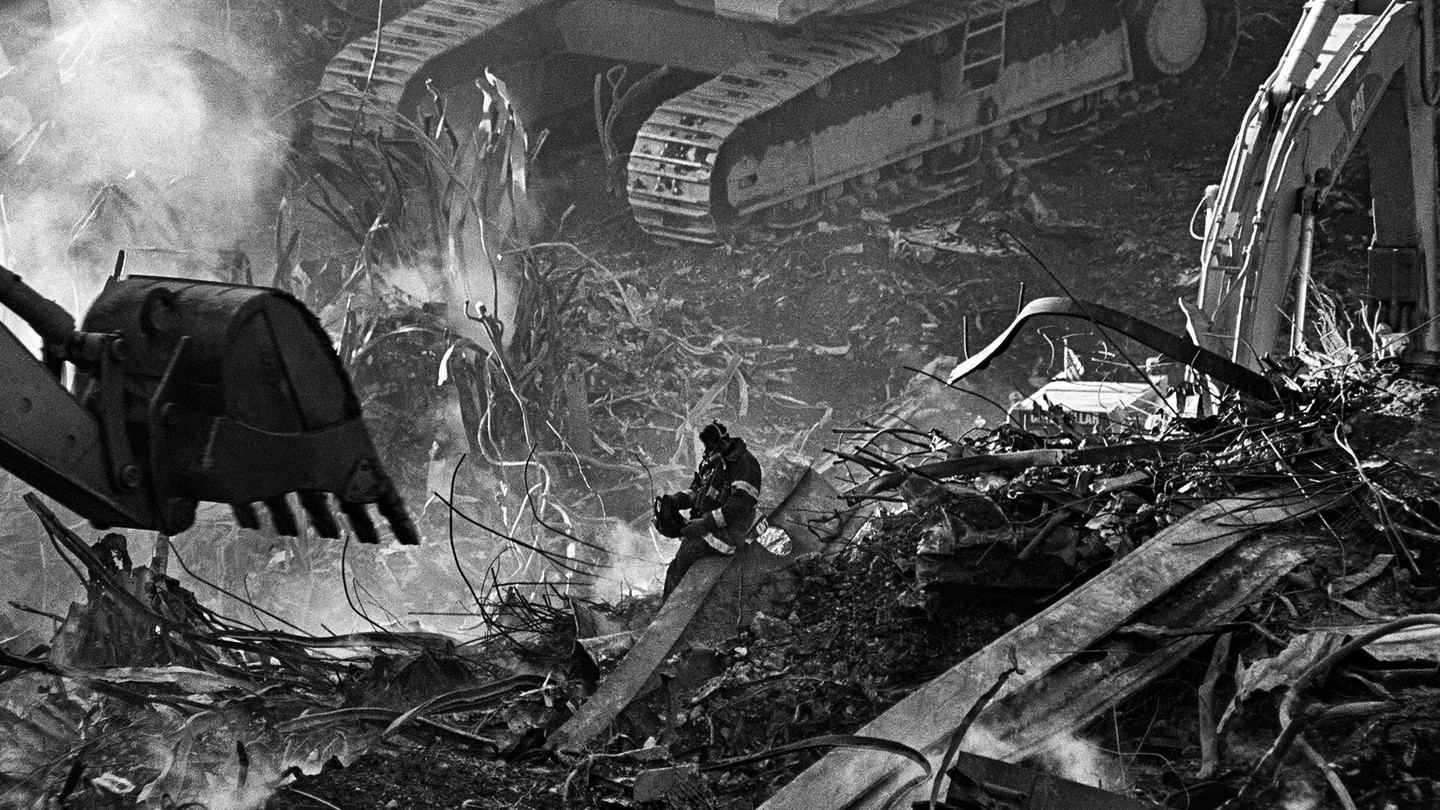 Photo of firefighter sitting on twisted metal wreckage surrounded by enormous excavators