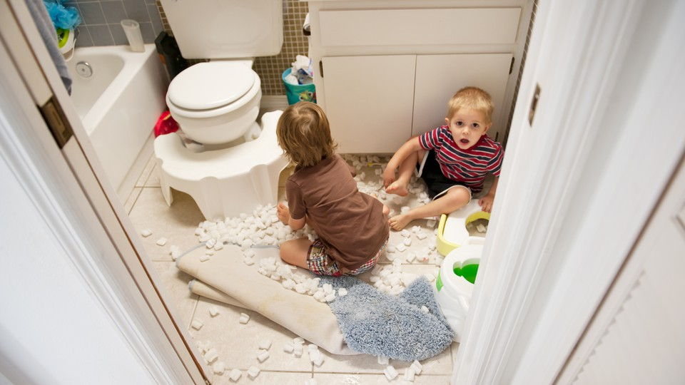 Two young children sit on the floor of a bathroom surrounded by packing peanuts. One child looks clearly alarmed and perhaps guilty of misbehavior.