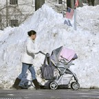 A woman, forced into the street by blocked sidewalks, pushes a stroller down a street in Boston.