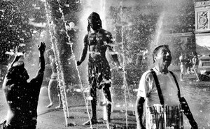A black-and-white photo of people in a fountain, by Clay Benskin