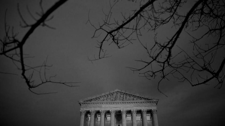 A photo of the Supreme Court building set against a dark and cloudy sky with bare tree branches framing it in the foreground