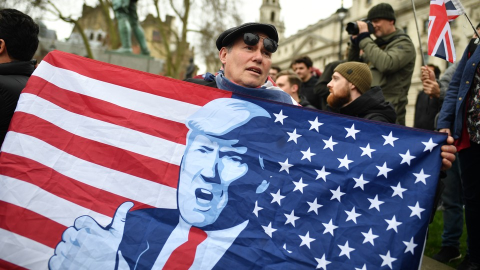 A man in London holds up a stylized American flag featuring Donald Trump