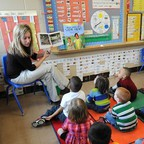 Preschool students listen to their teacher, Angie Clark, read at a Des Moines Iowa elementary school.