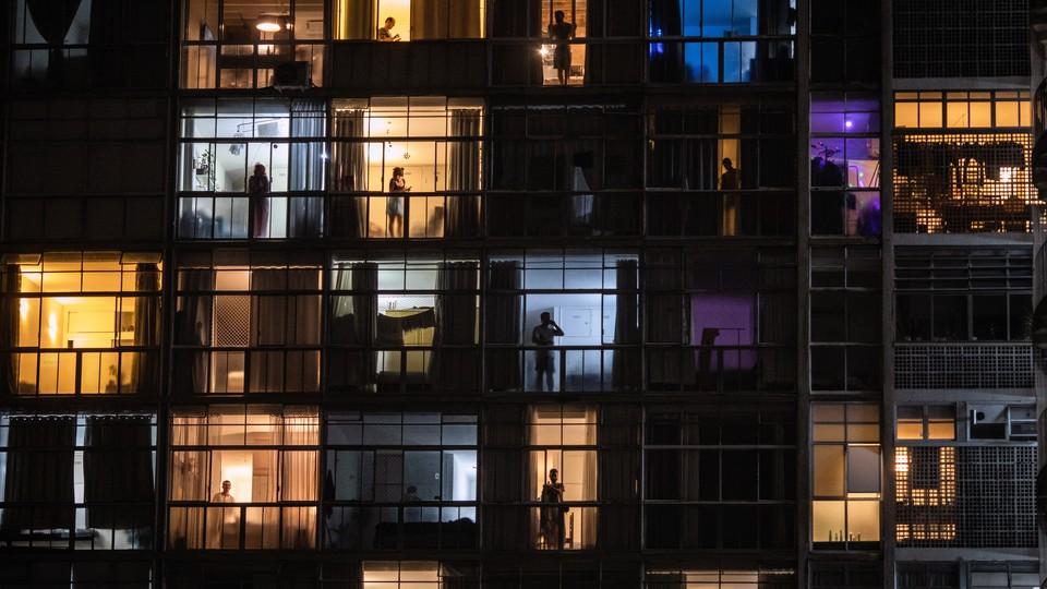 People in windows viewed through balconies