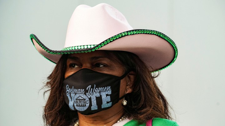 "A woman wearing a mask that says ""Vote"""