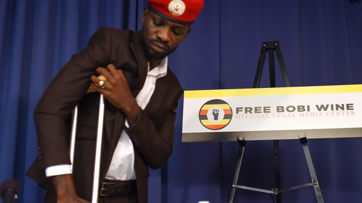 Bobi Wine stands with the support of a crutch as he gives a press conference in Washington, D.C., on September 6.