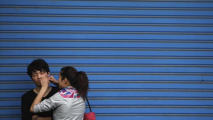 A woman pops a pimple on her boyfriend's face