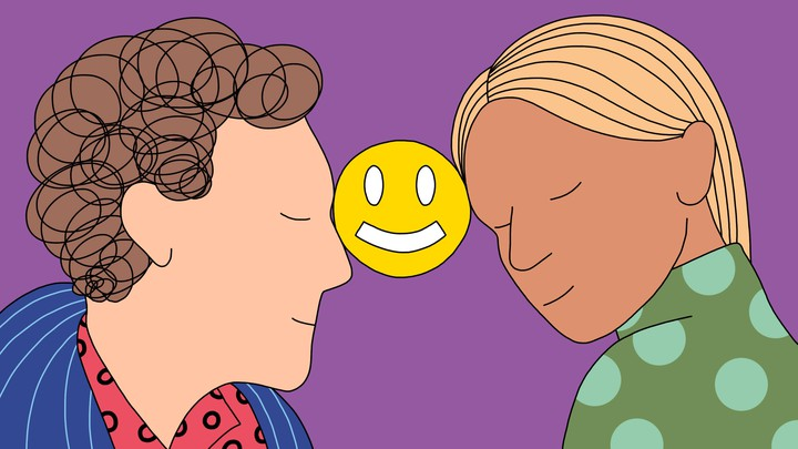 A man and a woman lean in smiling, holding a smiley face icon between their foreheads