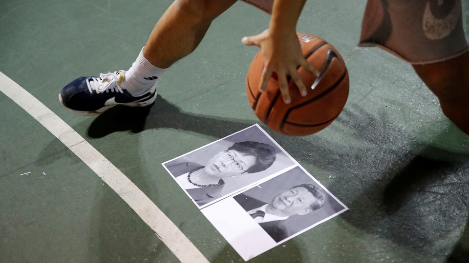 A basketball is dribbled over pictures of President Xi Jinping and Hong Kong Chief Executive Carrie Lam.