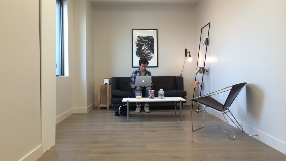 The author sits on a couch at his laptop in a Breather room.