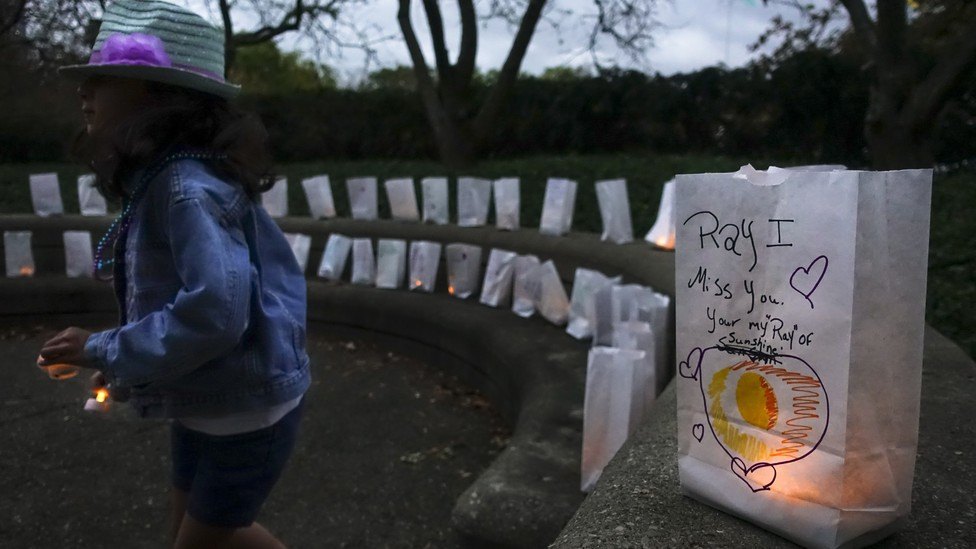 A woman lights a candle for someone who died by suicide.