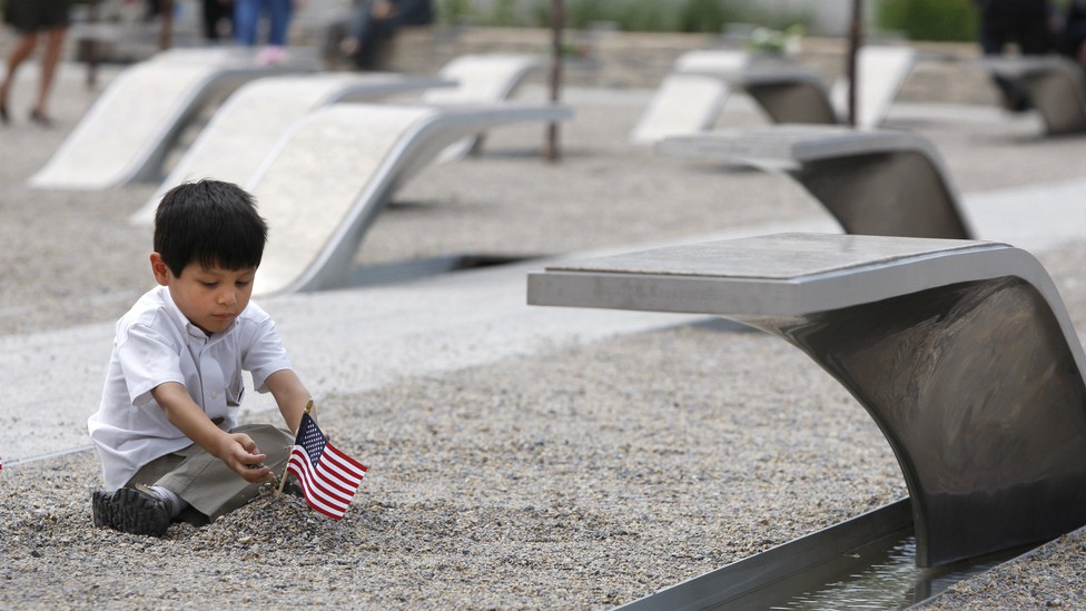 A child plays with a flag at the Pentagon's September 11 memorial.