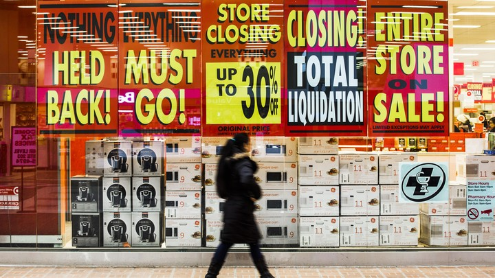A retail store with signs advertising a pre-closing clearance sale
