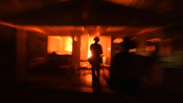 A firefighter surveys a burning house.
