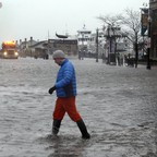 A man wades across State Street in Boston, flooded by water from Boston Harbor.