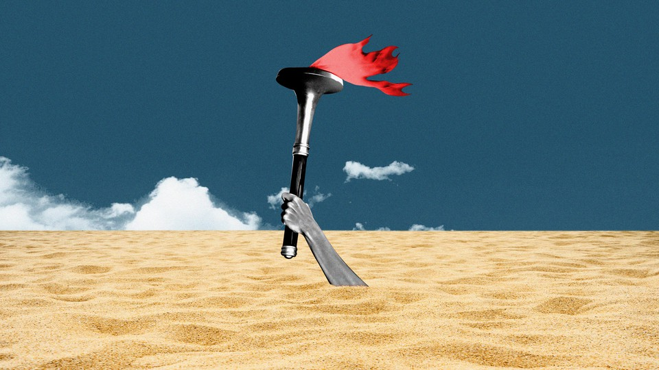 A hand bearing the olympic torch sinks beneath the sands