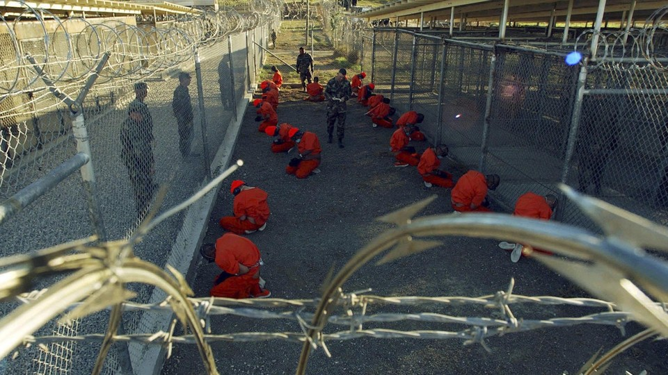 Detainees in orange jumpsuits sit in a holding area under the watchful eyes of military police during in-processing to the temporary detention facility at Camp X-Ray of Naval Base Guantanamo Bay on January 11, 2002.