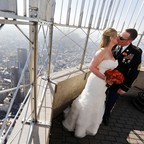 A husband and wife kiss on the Empire State Building after their Valentine's Day Wedding