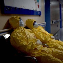 Two hospital workers in yellow hazmat suits rest on chairs in a dimly lit hallway