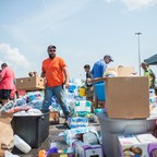 Men stand outside organizing water bottles, diapers, and other supplies into boxes.