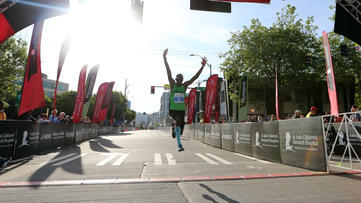 A runner excitedly crossing a finish line