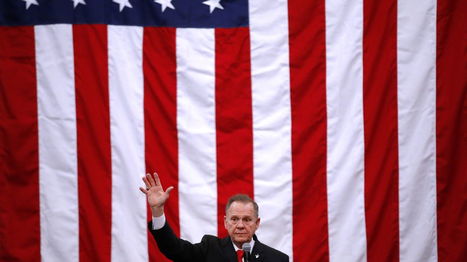 Roy Moore at a campaign rally with a giant American flag behind him