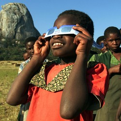 A girl looks through eclipse glasses.