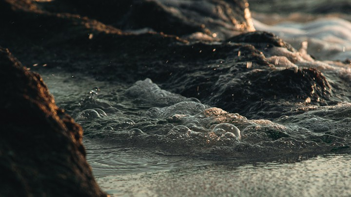 A photo of water swirling around basaltic rocks