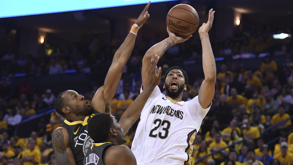 The New Orleans Pelicans forward Anthony Davis (23) shoots the basketball against Golden State Warriors forward Andre Iguodala (9) and forward Kevon Looney (5) in a May 1 game