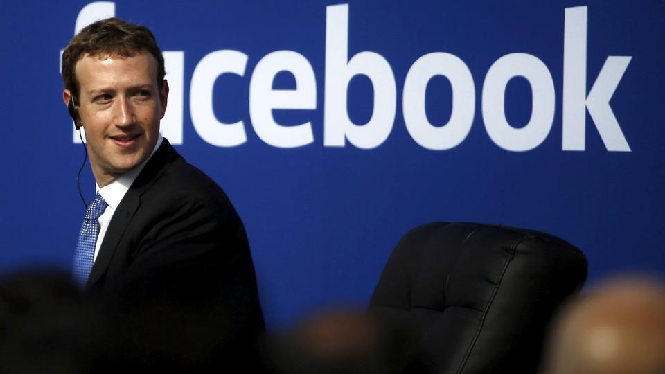 Mark Zuckerberg with the Facebook logo behind him