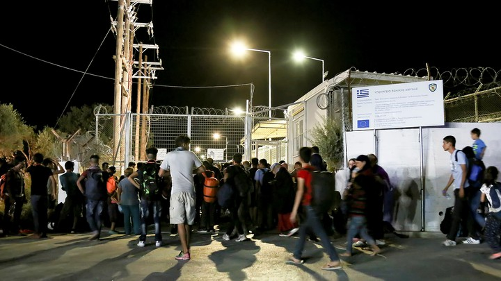Migrants gather outside a Lesbos refugee camp after a fire forced them to flee