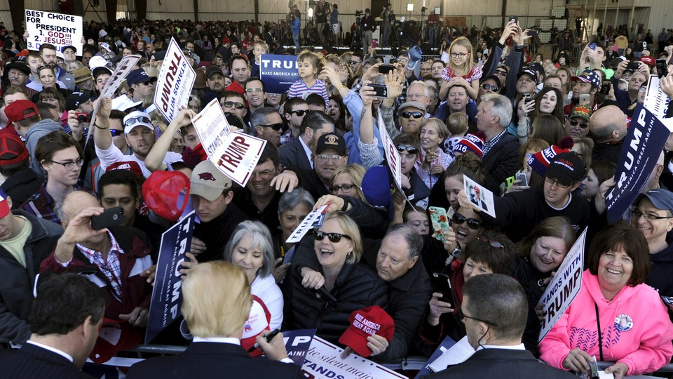 A crowd of people, many holding Trump signs, clamor to get Trump's attention, who is standing at the front of the crowd signing a hat.