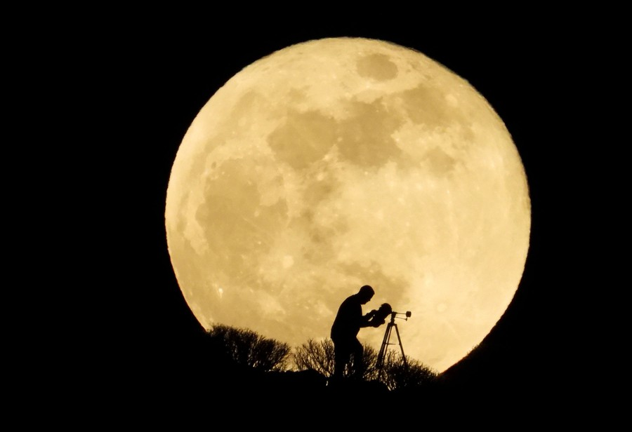 A person is seen in silhouette against a giant moon, pointing a telescope toward it.
