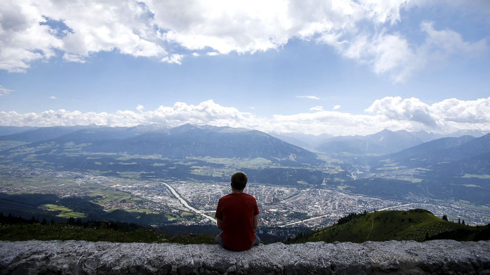 A man sits on a wall and enjoys the view.