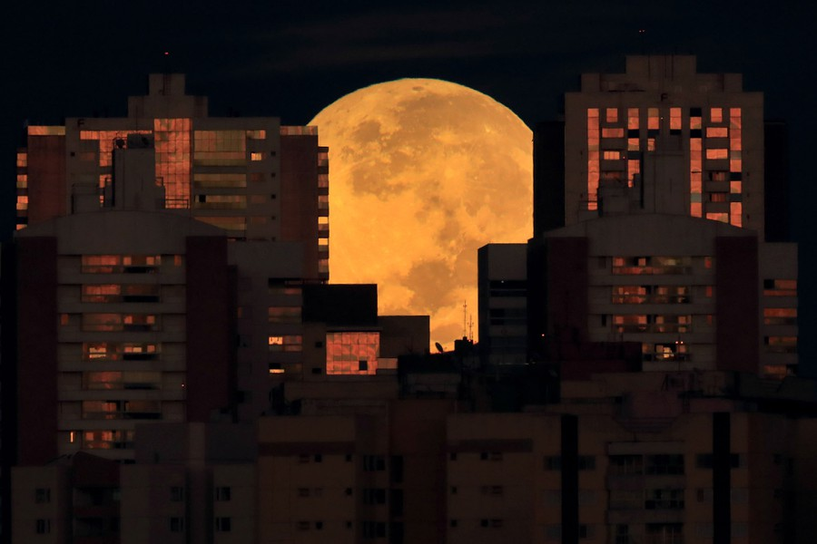 The full moon is seen behind tall buildings.