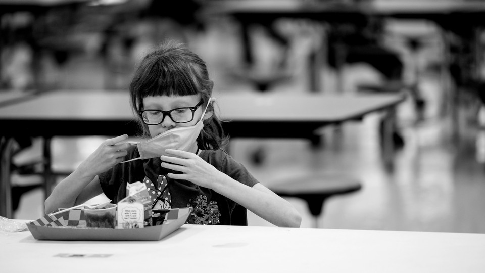 A girl taking off her mask to eat school lunch alone