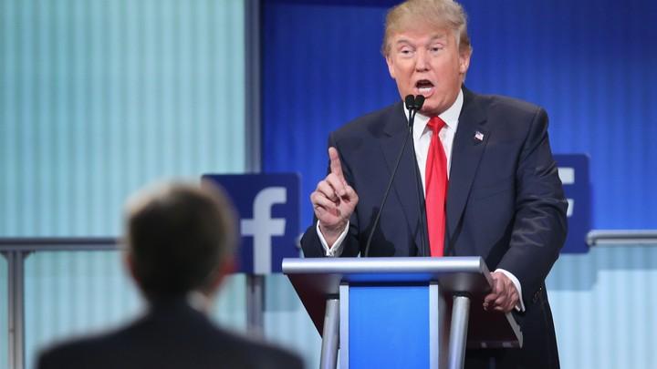 Donald Trump speaks at a podium next to a Facebook logo.
