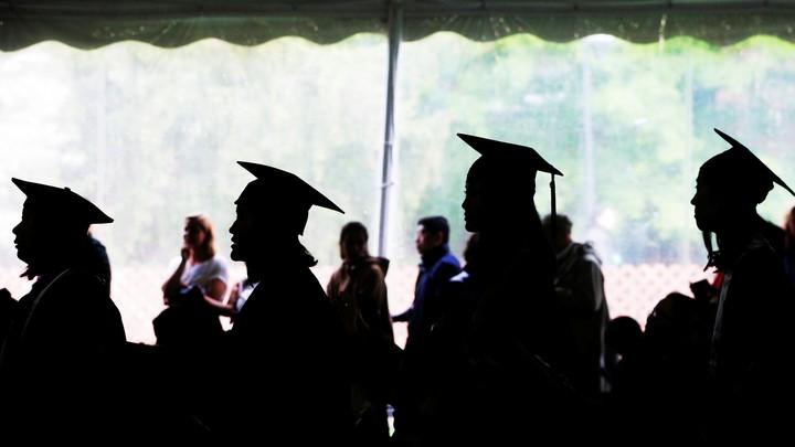 Female college graduates stand in a line.