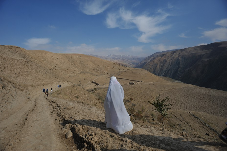 A woman walks along a rural road in a white Burqa