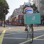 A man bikes down a busy London street with a food-delivery box on the back of his bike.
