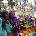 Two women in hijabs look at a cell phone in front of a row of boats with Spanish names.