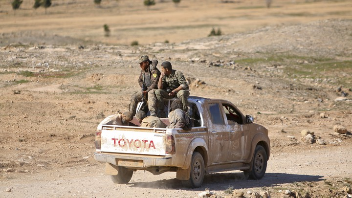 Fighters in the Syrian Democratic Forces ride a pickup truck with Islamic State fighters held as prisoners near al-Shadadi town, in the Hasaka countryside of Syria, on February 18, 2016.