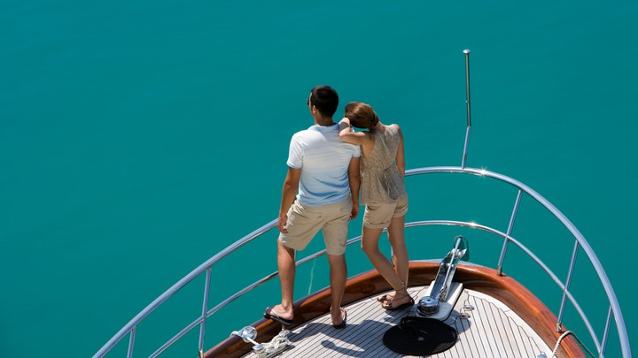 A couple on a yacht looks out at the water.