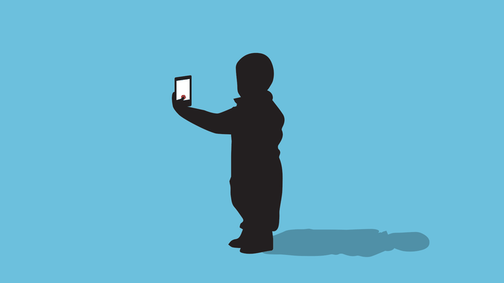 A small child takes a selfie on a smartphone.