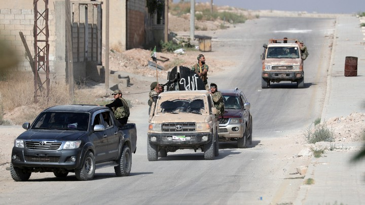 Turkey-backed Syrian rebel fighters ride on vehicles on a dusty road.
