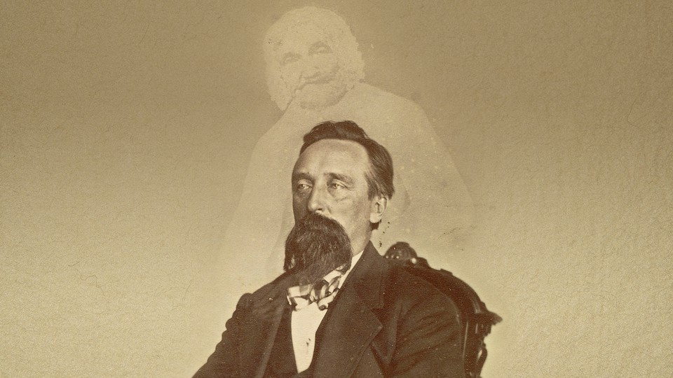 A vintage photo of a bearded man with the ghostly image of another person superimposed