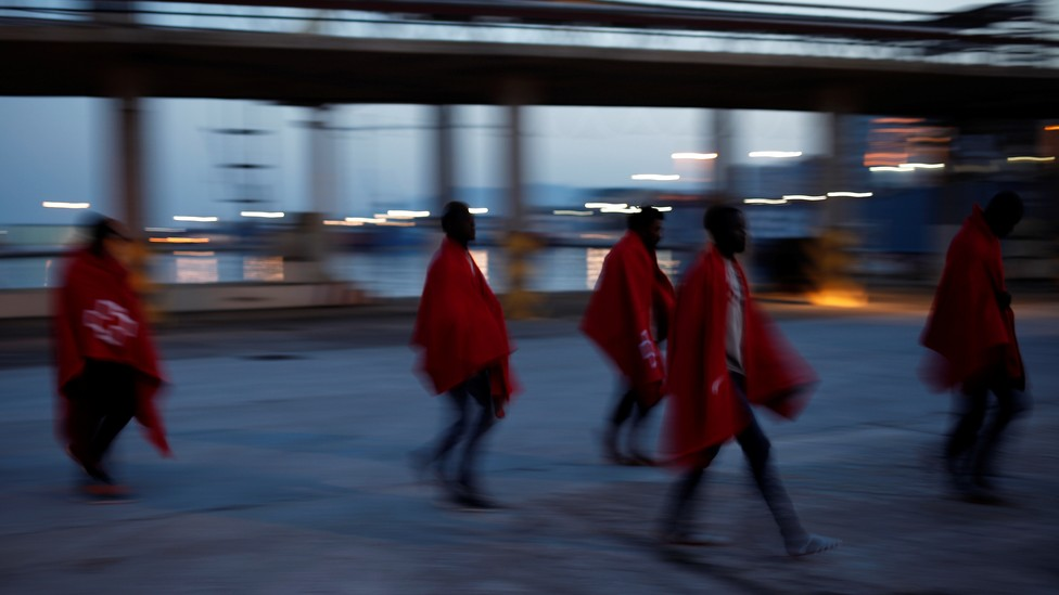 Five young migrants wearing Red Cross blankets walk in the Port of Malaga.